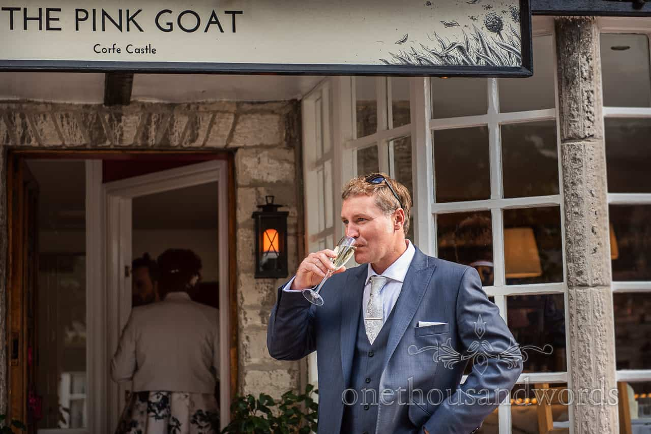 Groom in three piece blue wedding suit drinks champagne outside The Pink Goat restaurant in Corfe Castle