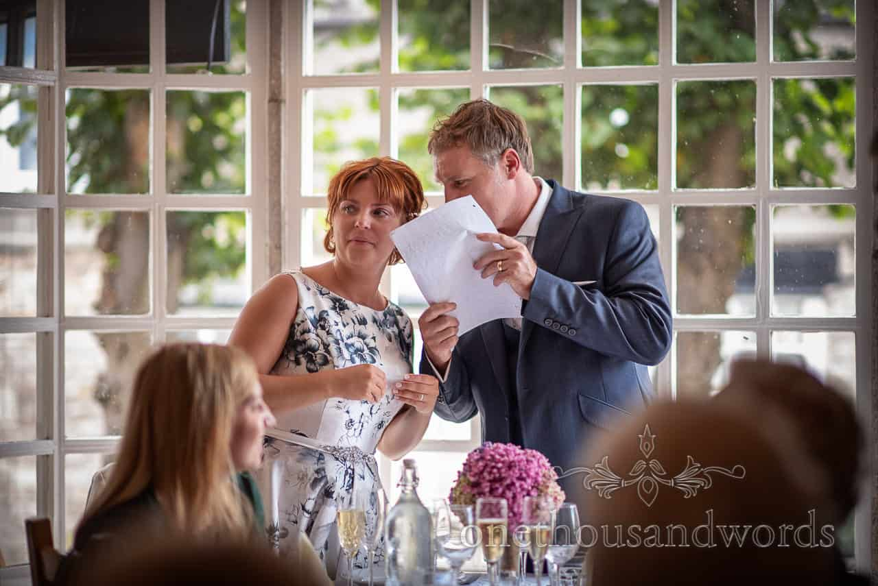 Groom whispers to bride behind wedding speech notes