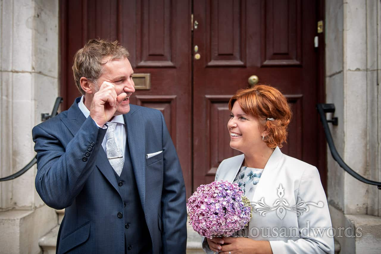 Groom cries tears of joy as bride laughs outside Swanage Town Hall wedding venue