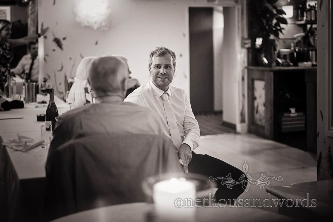 Black and white documentary wedding photograph of wedding guest enjoying an evening reception conversation