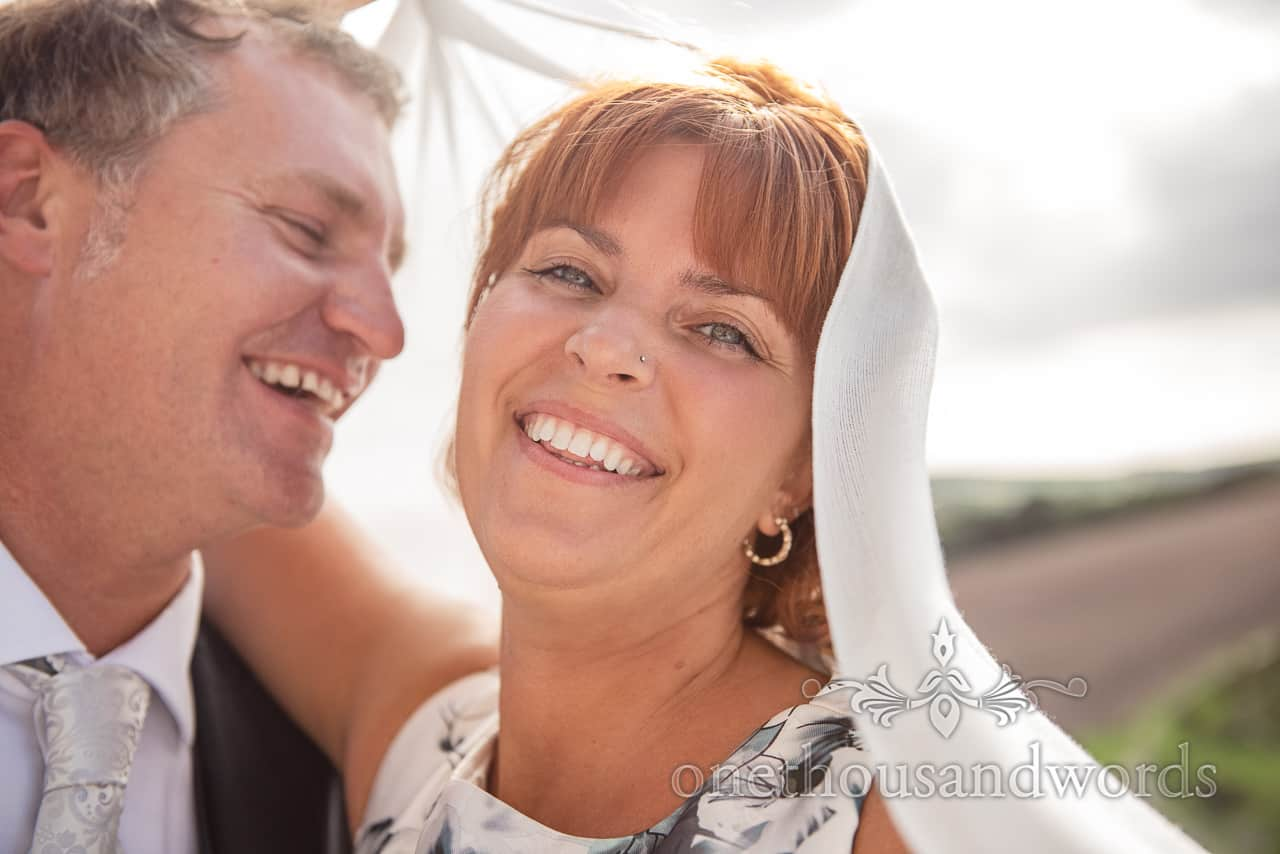 Laughing bride and groom close up portrait photograph under white wedding shawl