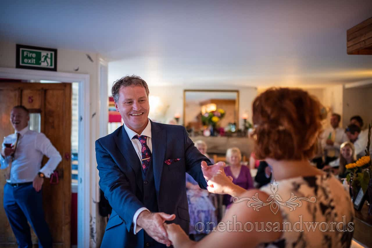 Happy groom enjoys jazz dancing with bride watched by laughing guests