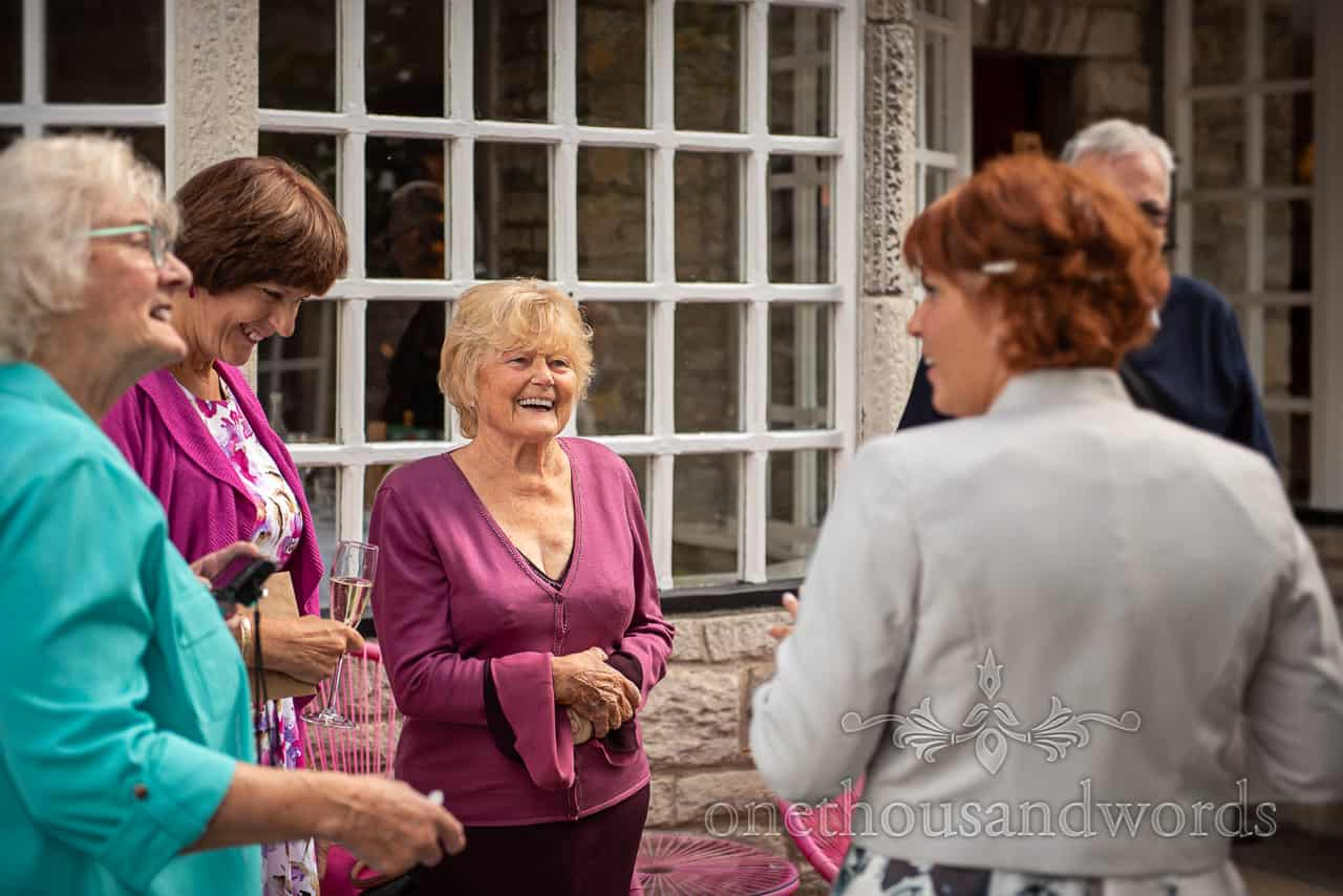 Laughing bride and guests outside Dorset restaurant wedding venue