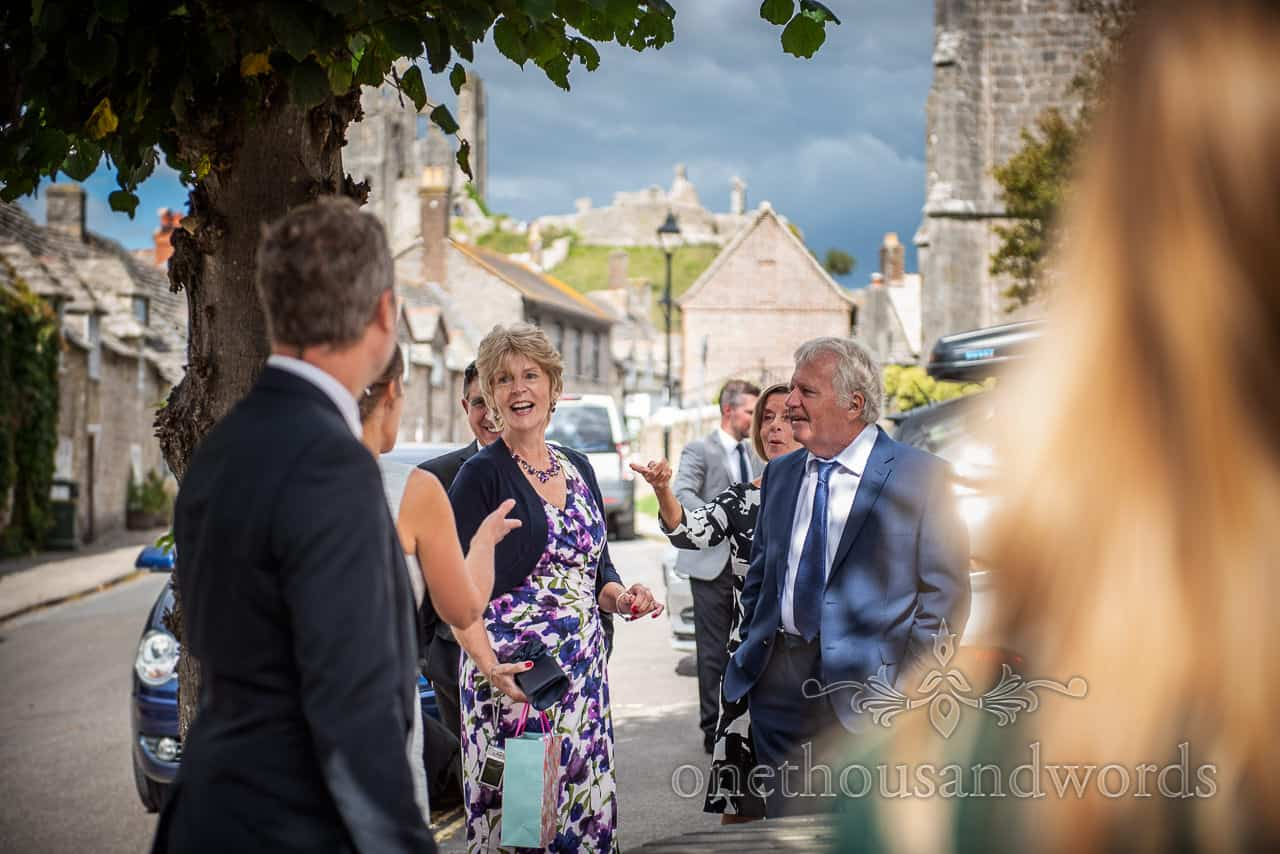 Laughing wedding guests wait outside Corfe Castle restaurant