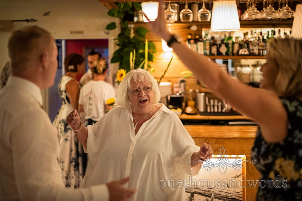 Female wedding guest in white shirt top dancing on wedding evening by a bar