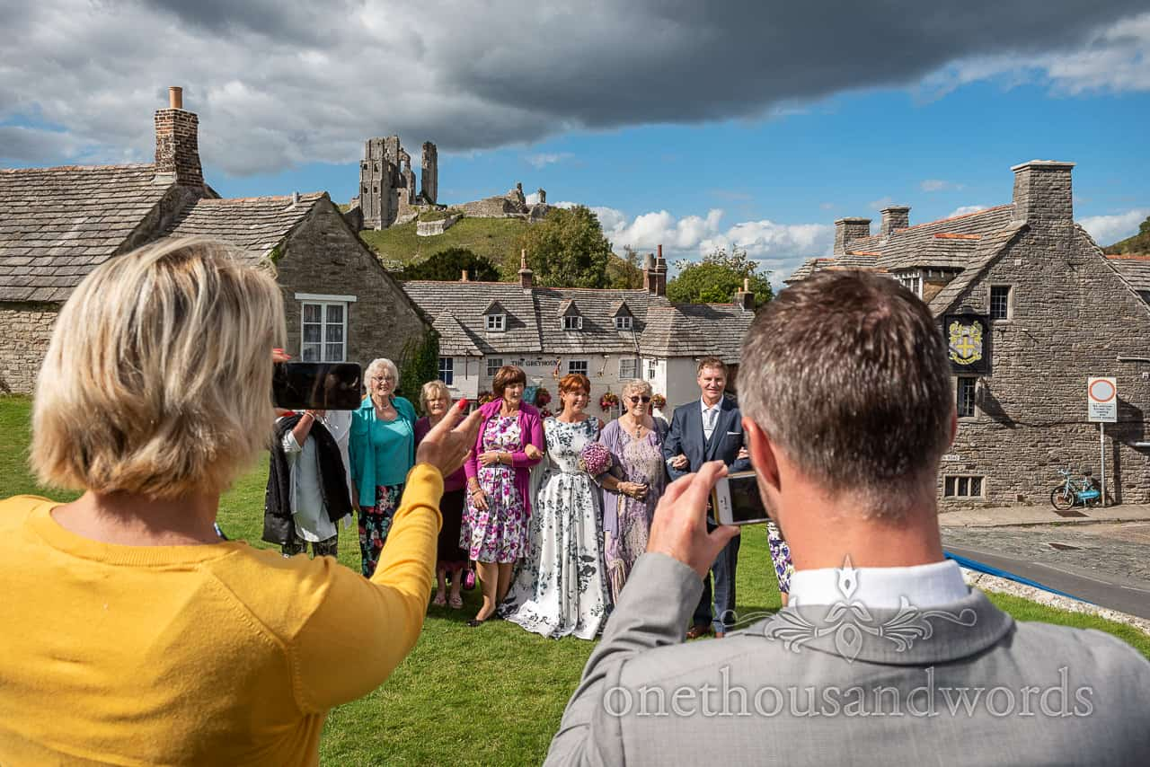 Wedding group photographs are directed by wedding guests in Corfe Castle village in Dorset