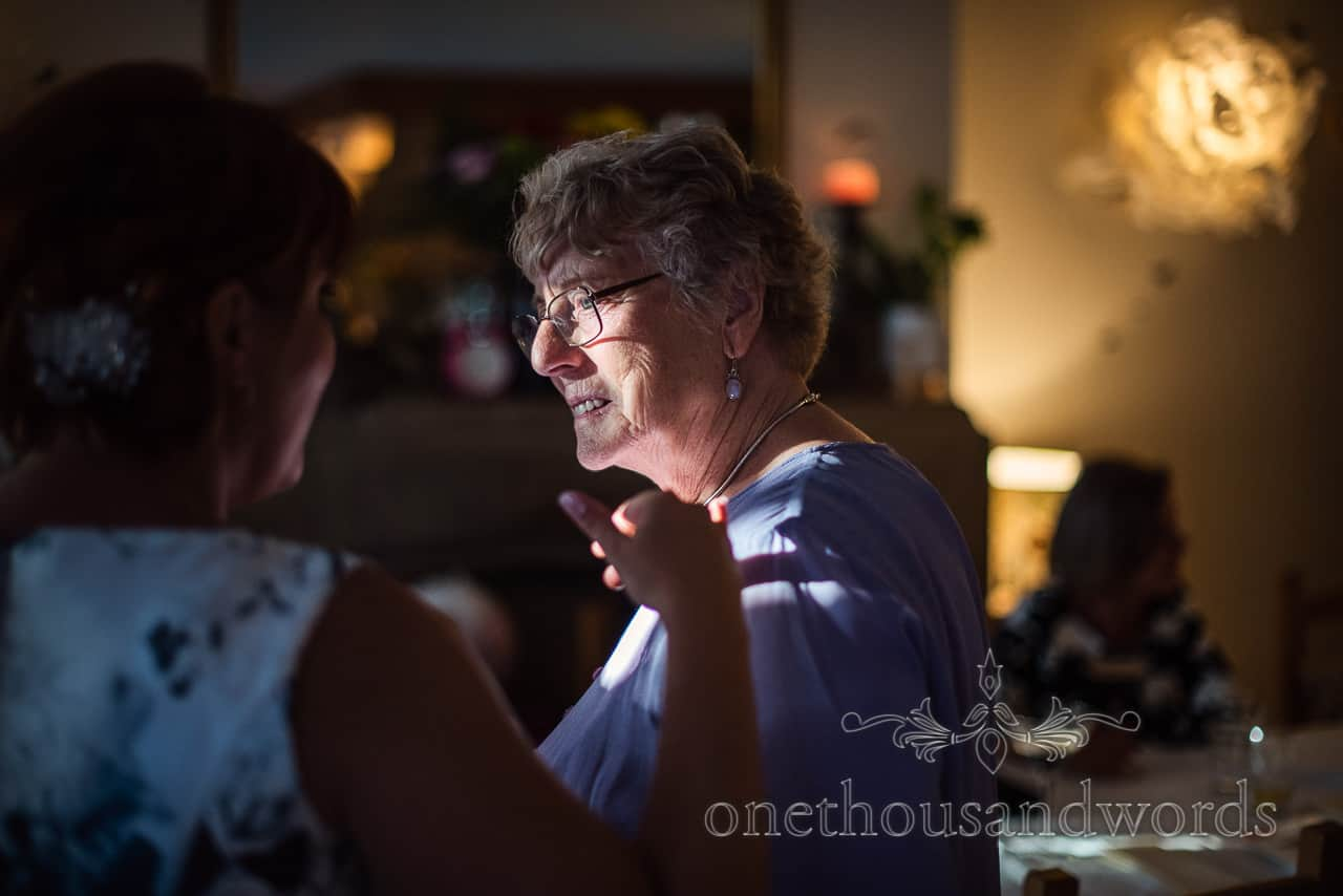Portrait photograph of female wedding guest in shaft of bright light