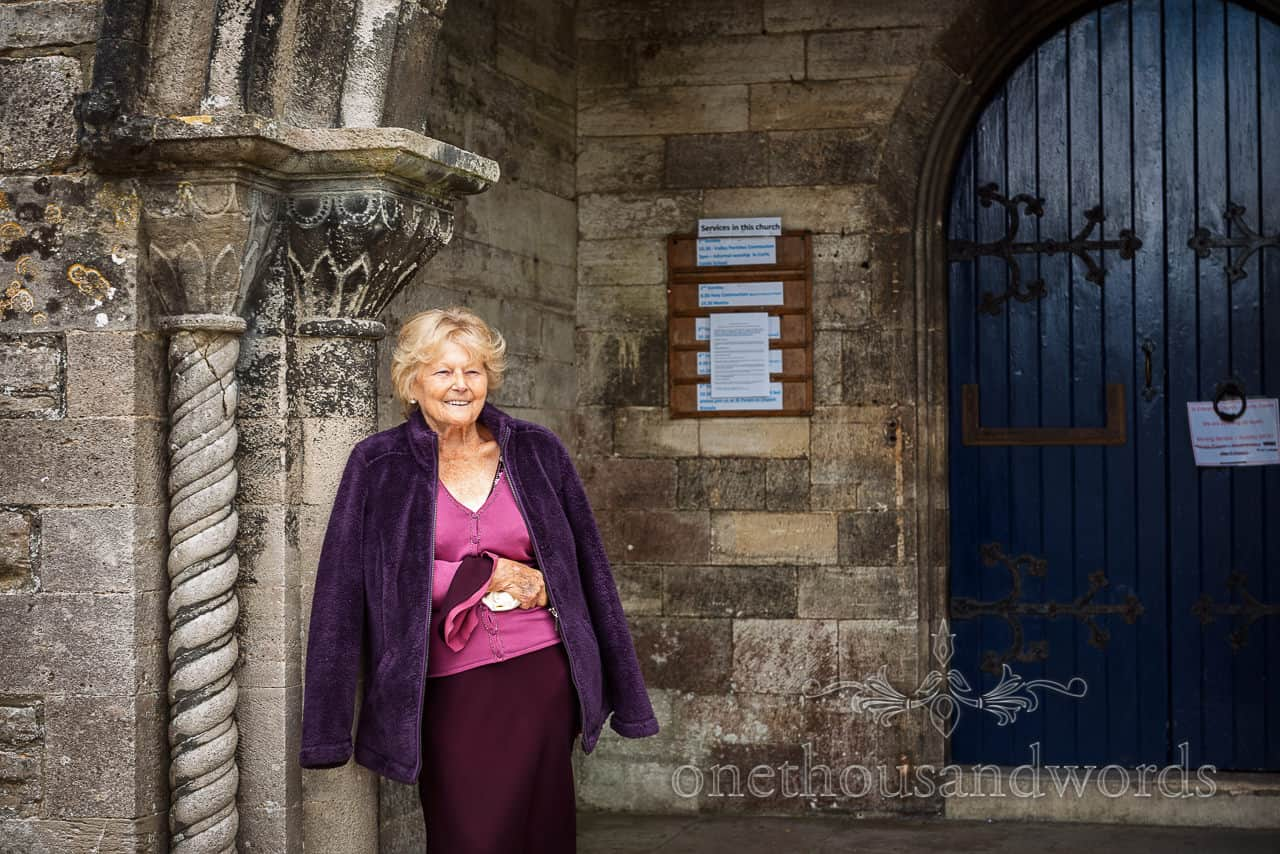 Wedding guest in purple waits outside Dorset stone church