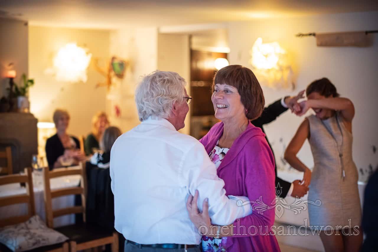 Smiling wedding guests learn swing dancing in Dorset restaurant