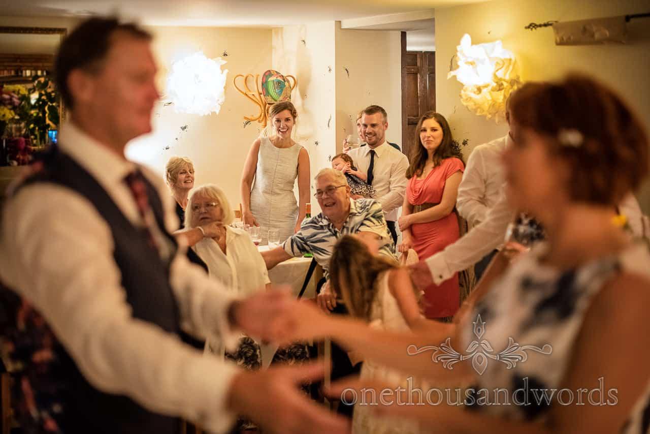 Wedding guests happily watch bride and groom dancing