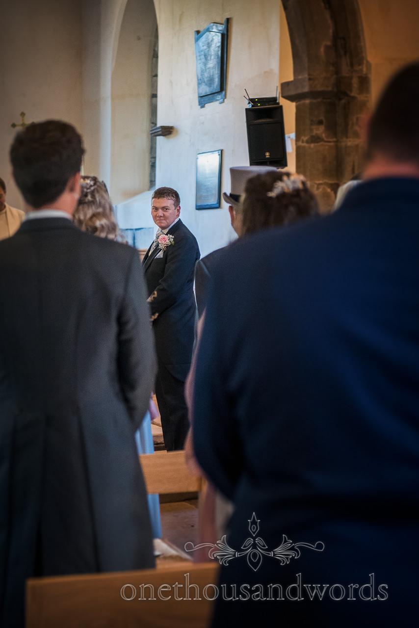 Grooms first look at bride walking down church aisle