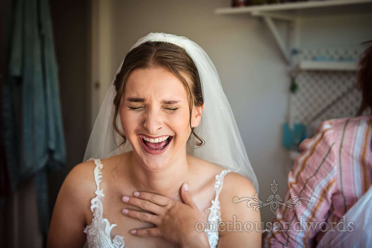 Bride in white veil and dress laughing on wedding morning portrait photo