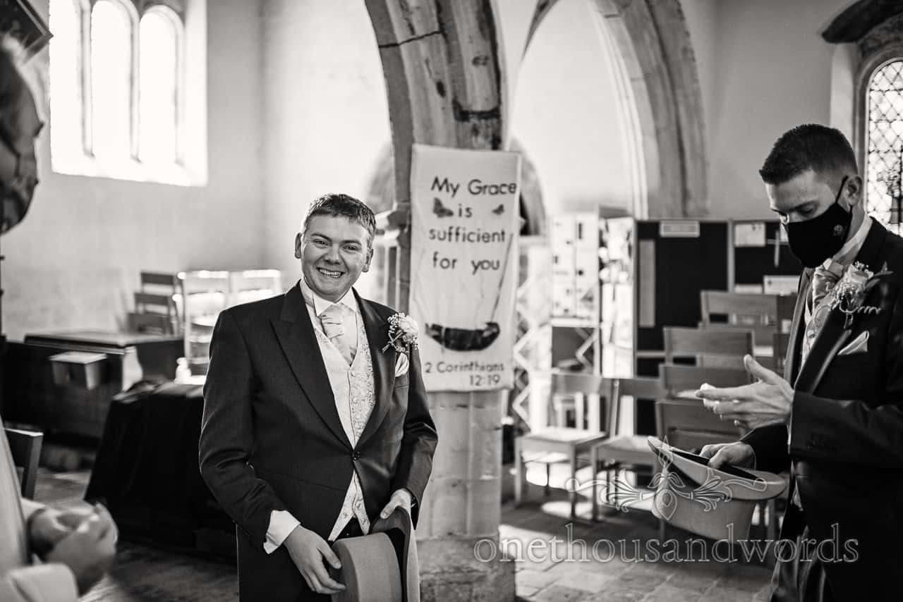 Black and white wedding photo of groom waiting for wedding guests in church