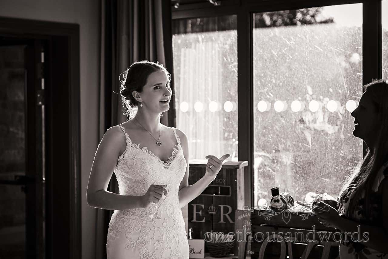 Black and white wedding photograph of bride haloed by sun