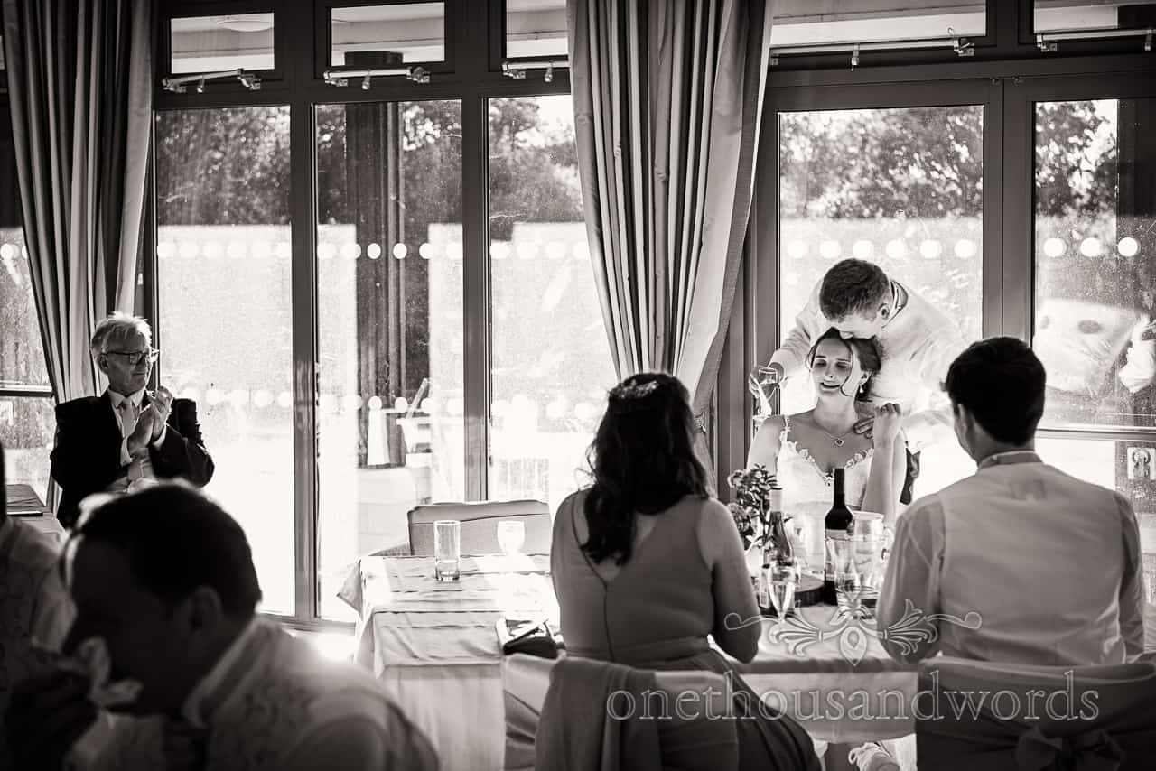 Black and white village hall wedding photographs of groom kissing bride on the head after wedding speeches in the village hall