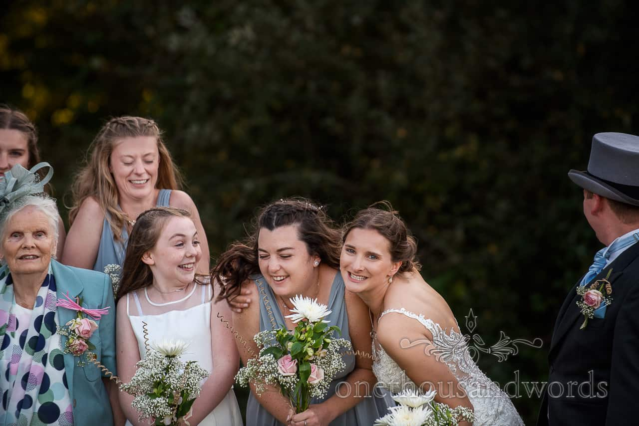 Bride and bridesmaid play together during wedding group photographs