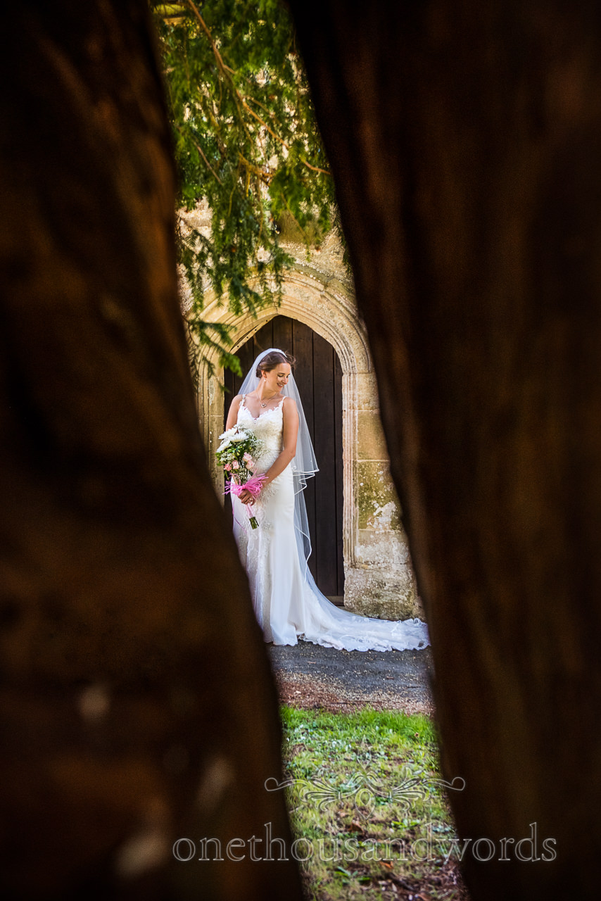 Bride stood in church doorway photo taken through bows of large yew tree