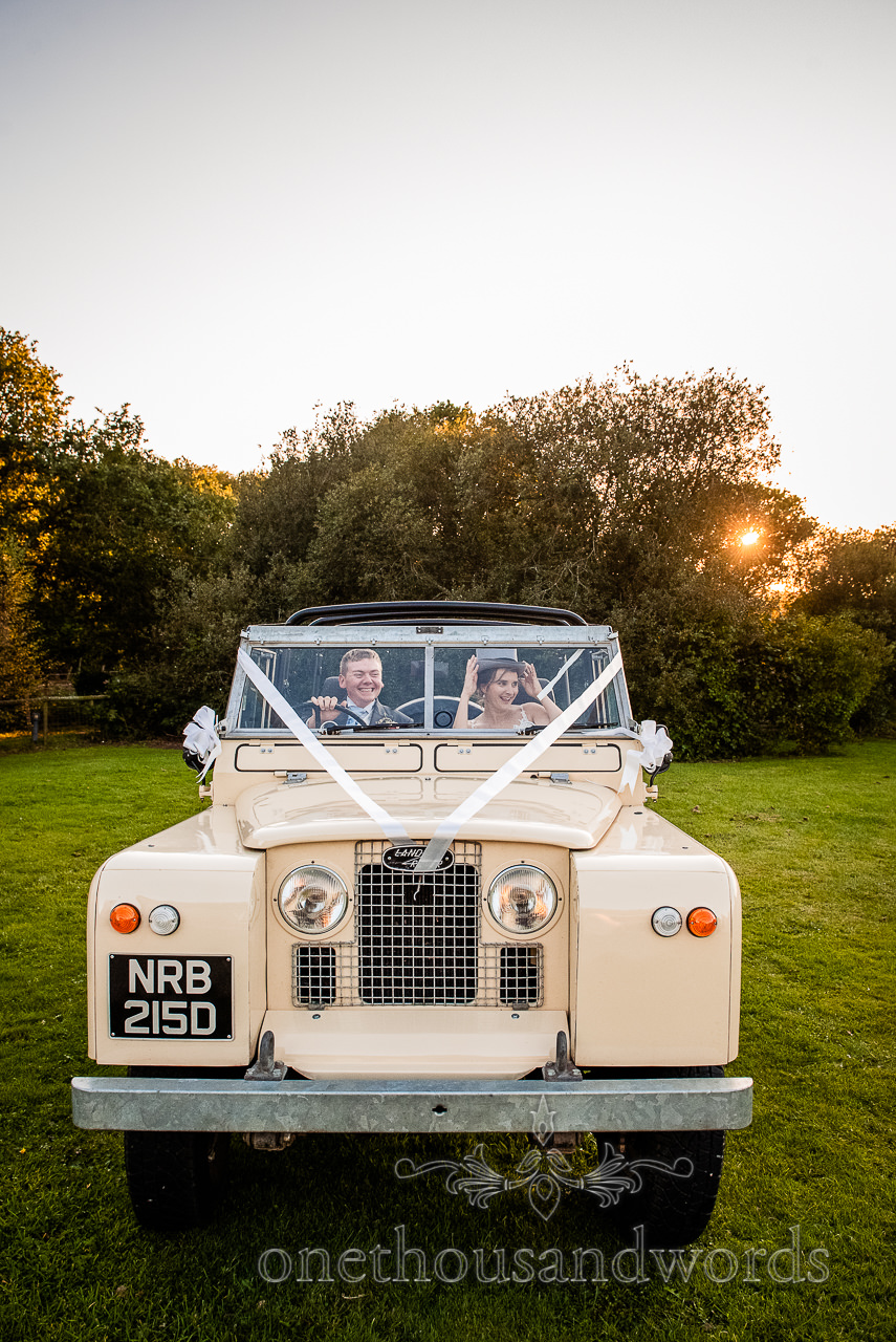 Bride and groom in classic Landrover wedding car