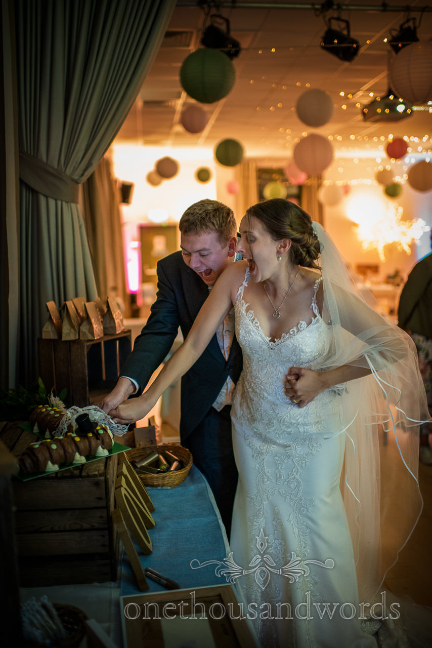 Village hall wedding photographs. Bride and groom laugh excitedly as they cut their wedding cakes