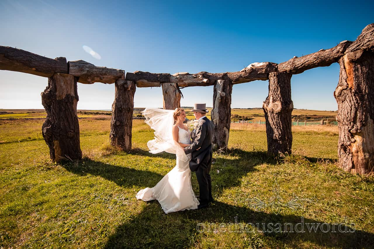 Bride and groom embrace in wood henge as wind blows the veil