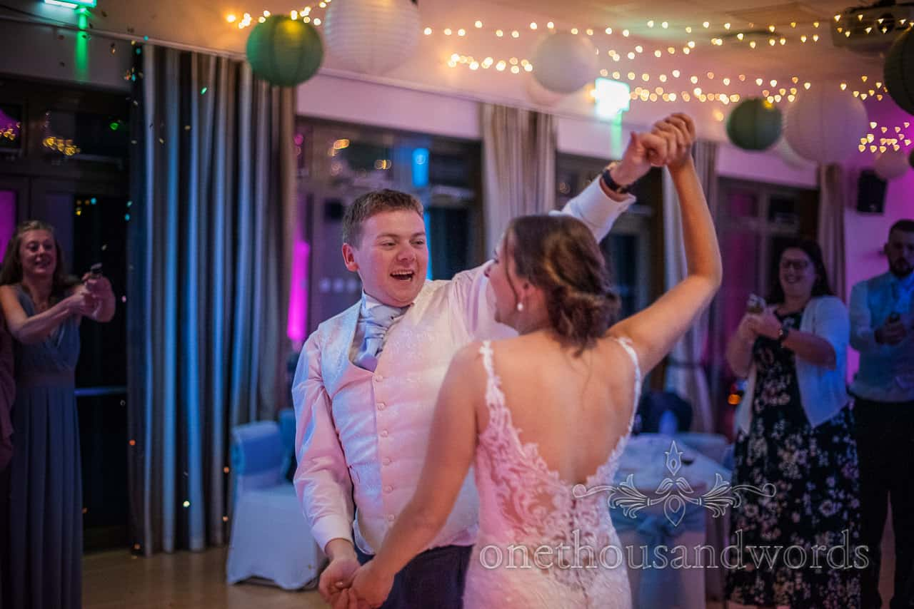 Bride and groom take first dance under coloured disco lights as guests aim confetti cannons