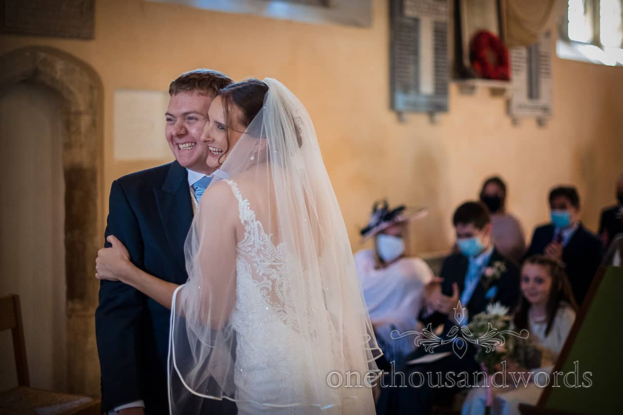 Bride and groom hug and squish faces in church wedding ceremony