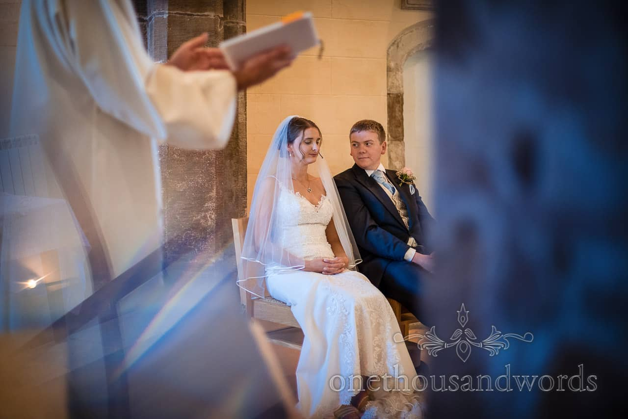 Bride and groom sit during church wedding ceremony in Dorset