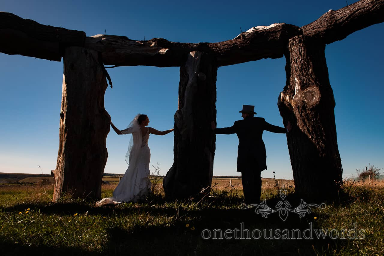 Bride and groom in silhouette photograph at wood henge Dorset