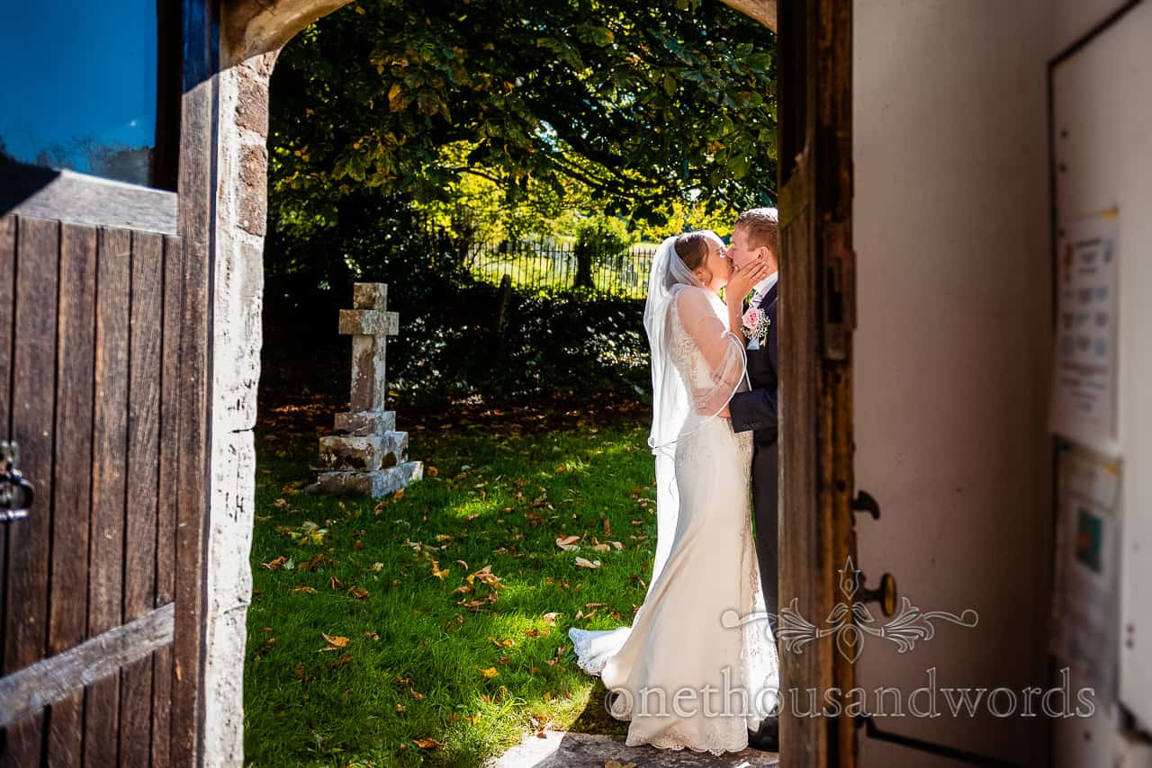 Bride and groom have a passionate kiss outside church doorway