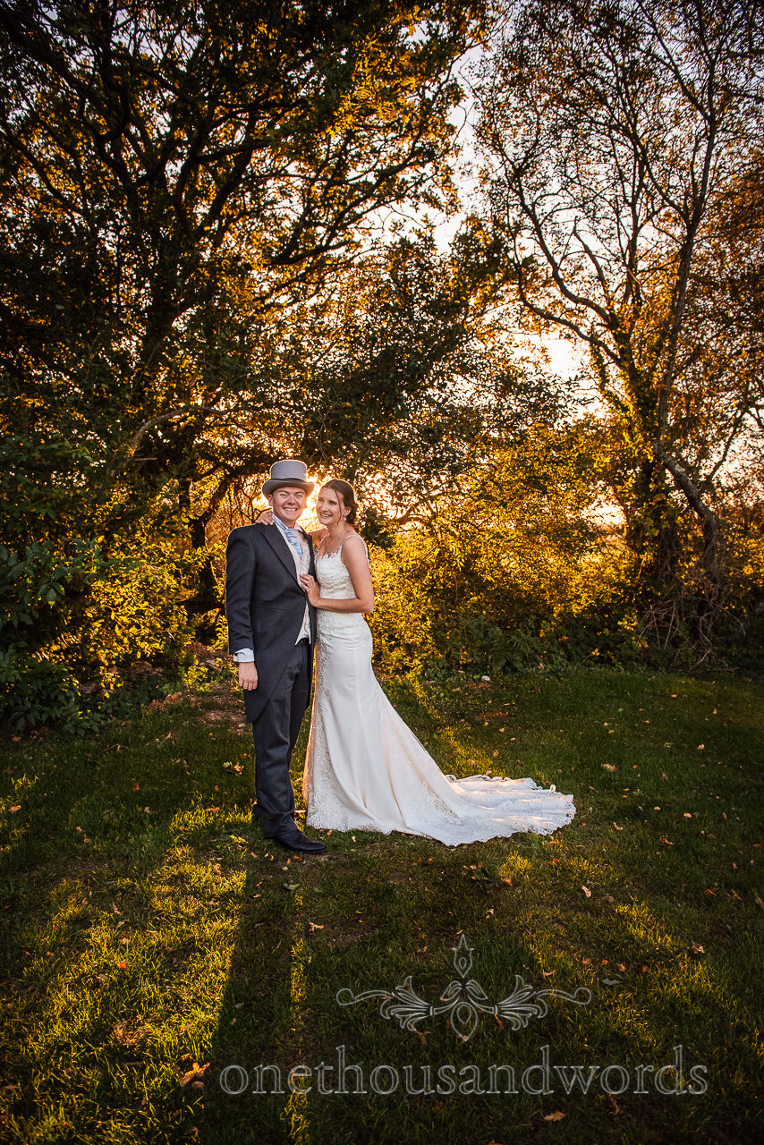 Bride and groom pose at sunset with light shafting through trees