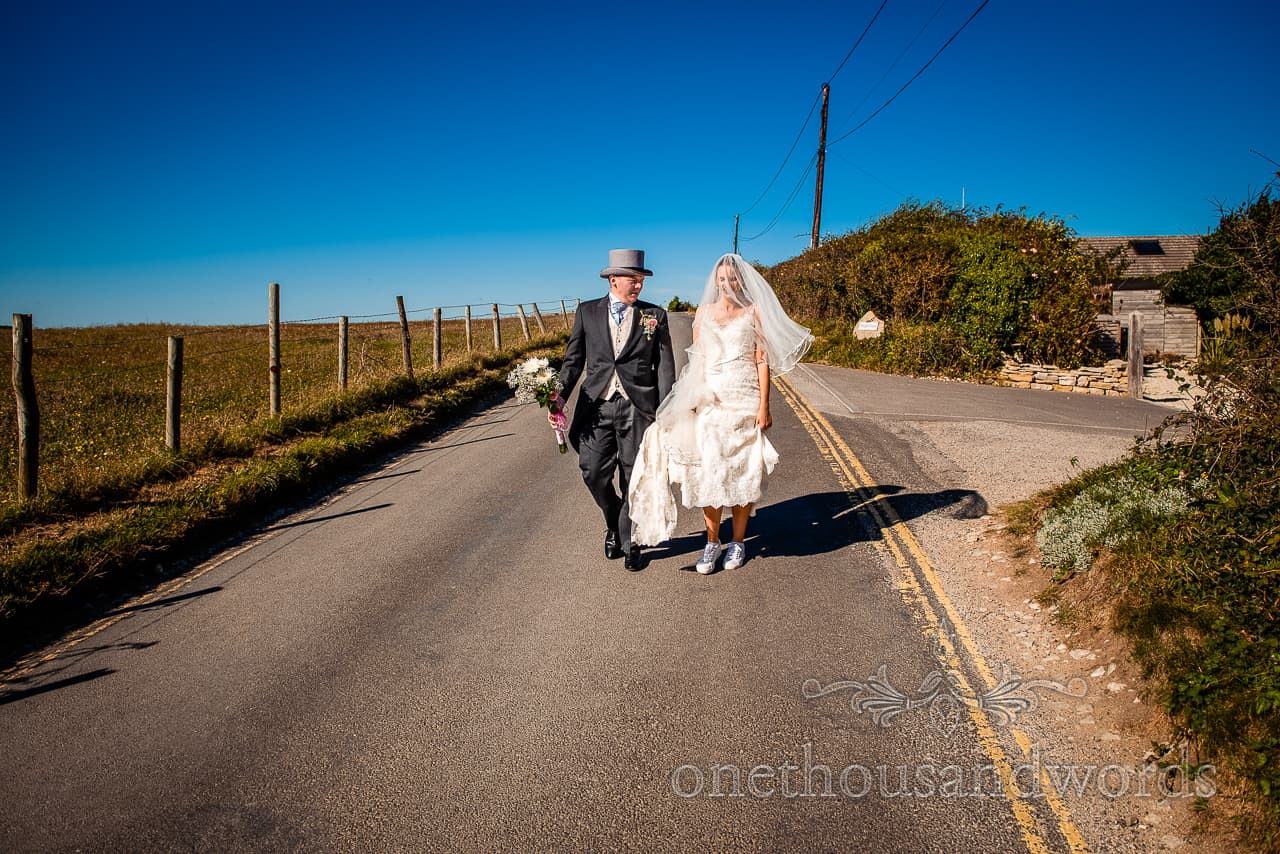 Bride and groom walk along Dorset countryside road