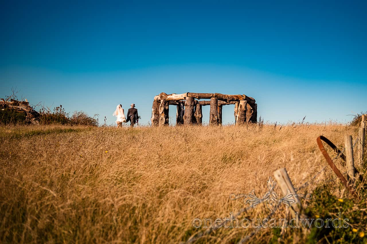 Bride and groom walk through long grass to wooden henge in Dorset countryside