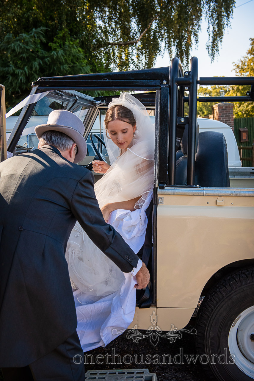 Bride is helped out of classic Landrover wedding car by her father