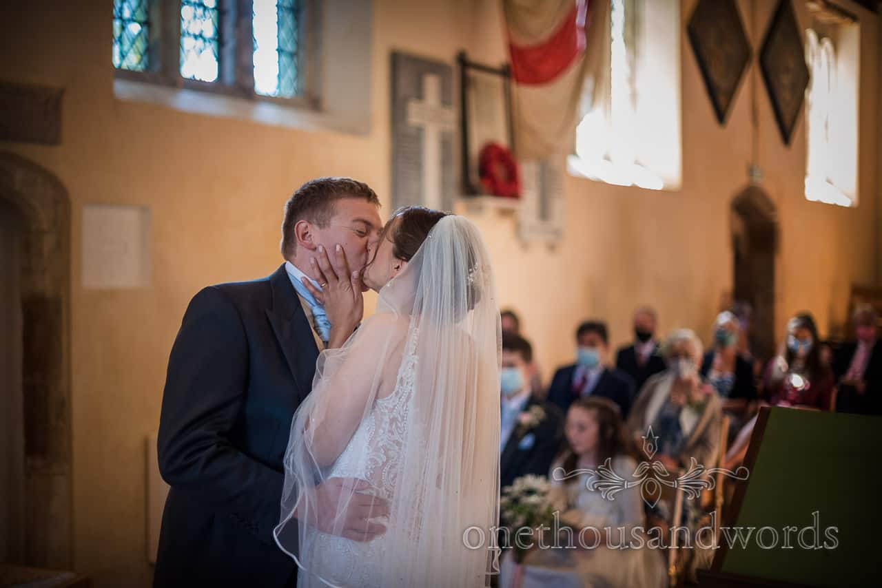 Bride holds groom's face as they have first kiss in church wedding ceremony