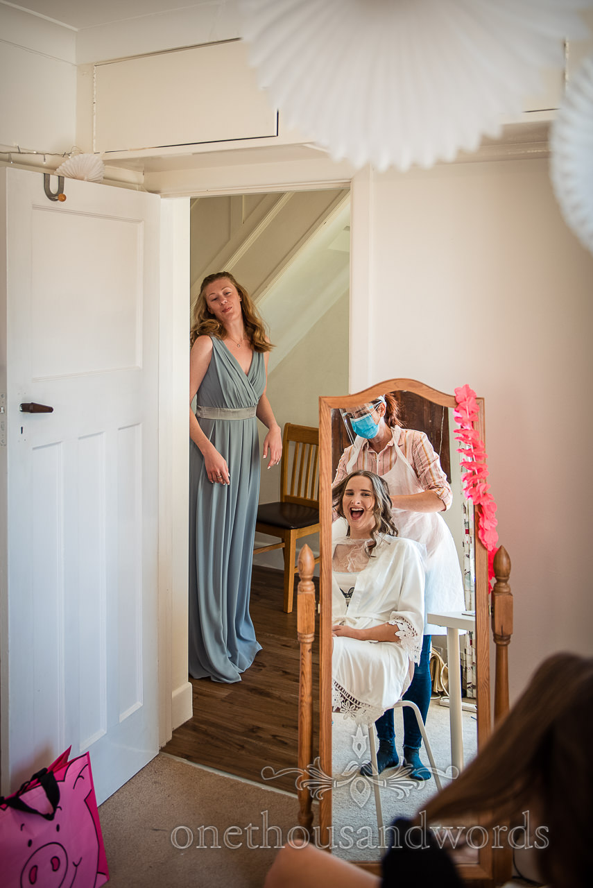 Reflection of the bride in a long mirror laughing at bridesmaid in a doorway during wedding morning preparation