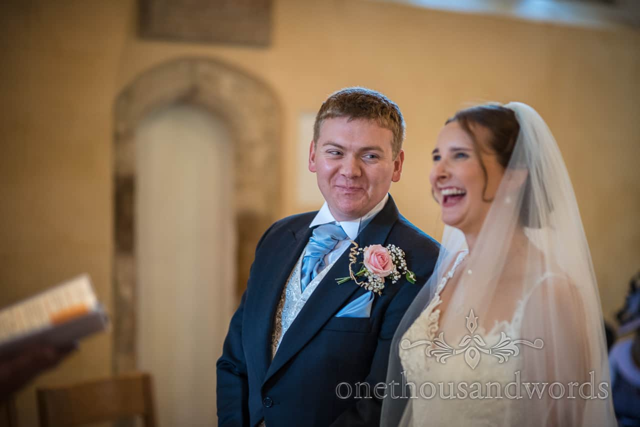 Groom takes a cheeky look at his bride laughing during church wedding vows