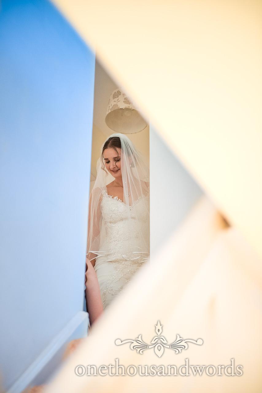 Wedding portrait photo of bride standing in corridor at top of stairs