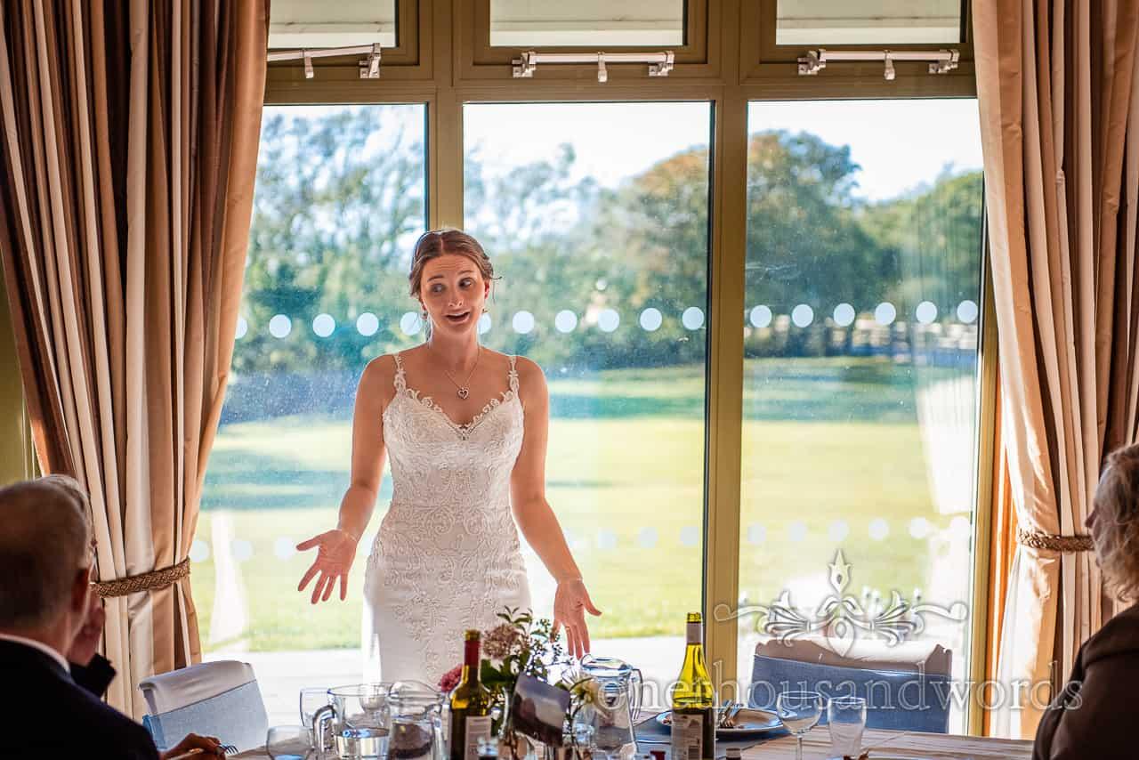 Bride in white shoulder strap dress stands talking to wedding guests