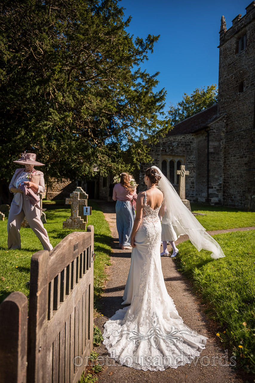 Bride in white trumpet wedding dress arrives at countryside village church