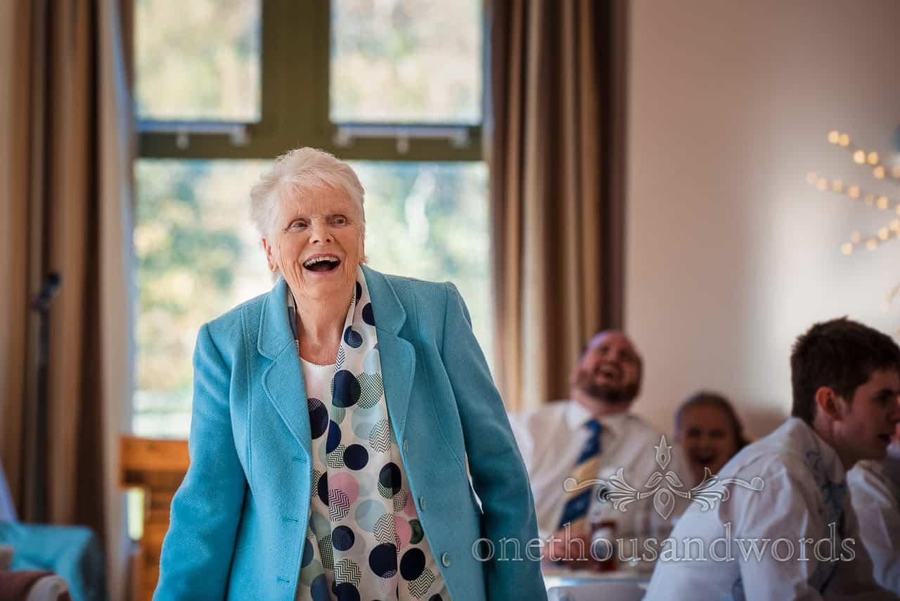 Bride's grandmother in blue jacket laughs at jokes during village hall wedding breakfast