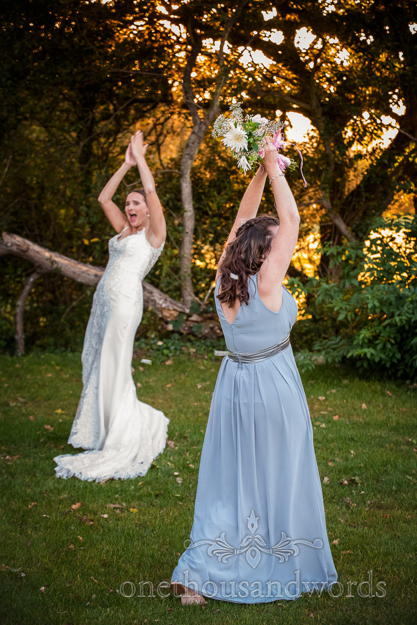 Bridesmaid in mint dress catches wedding bouquet as bride claps in background