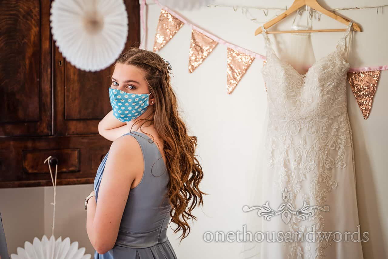 Bridesmaid in blue COVID face mask with daisy print on wedding morning