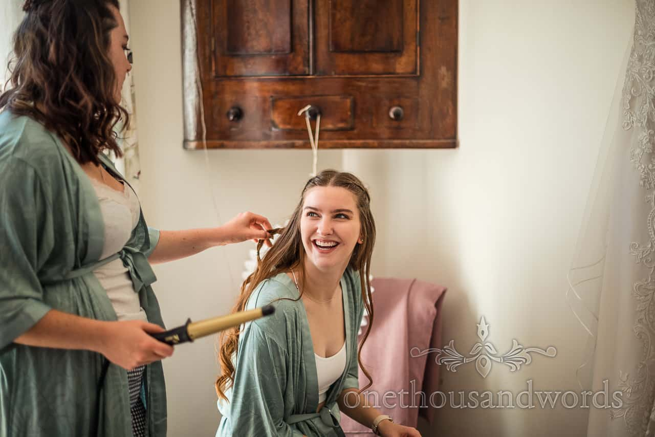 Bridesmaid in green dressing gown laughs as she has her hair curled on wedding morning