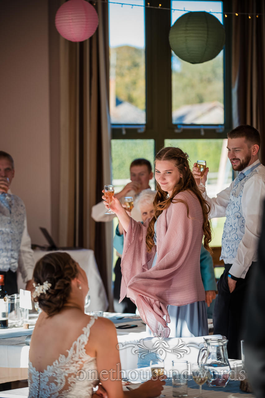 Bridemaid in dusty pink shawl looks at bride as she raises a glass to wedding speeches
