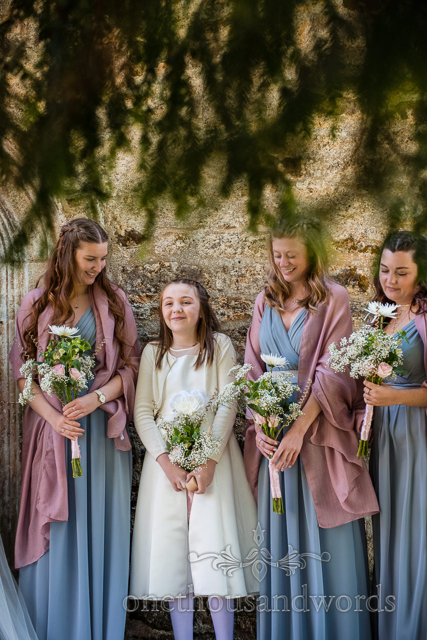 Bridesmaids in mint green dresses look at smiling flower girl