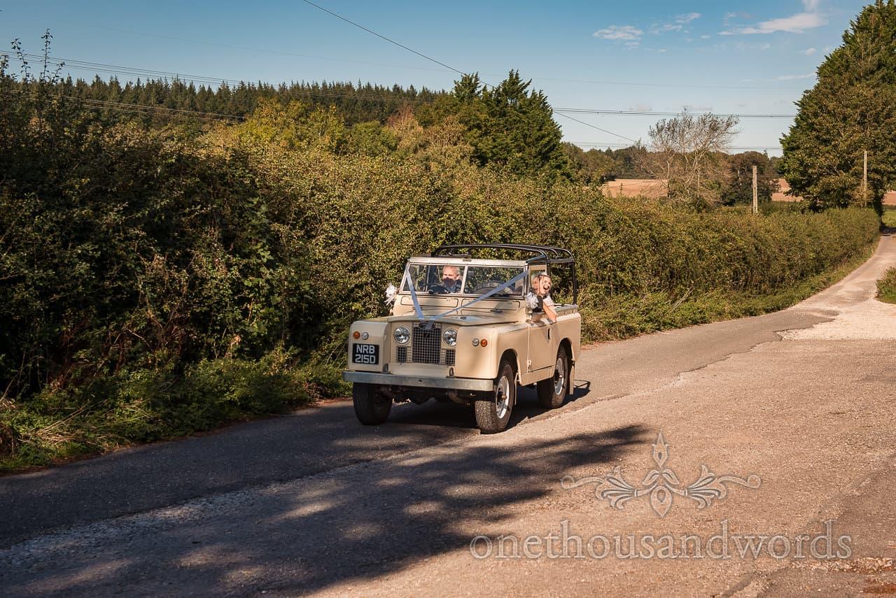 Classic wedding car landrover driving through countryside lanes