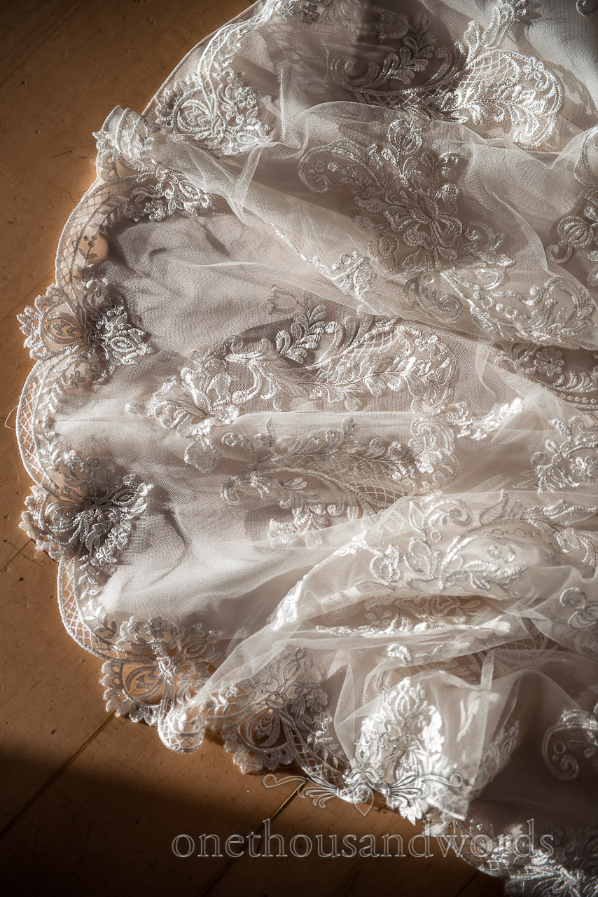 Close up detail photograph of wedding dress train lace patterns in low sun