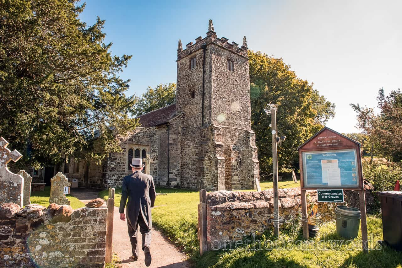 Groom in top hat and tails arrives at English countryside village stone church