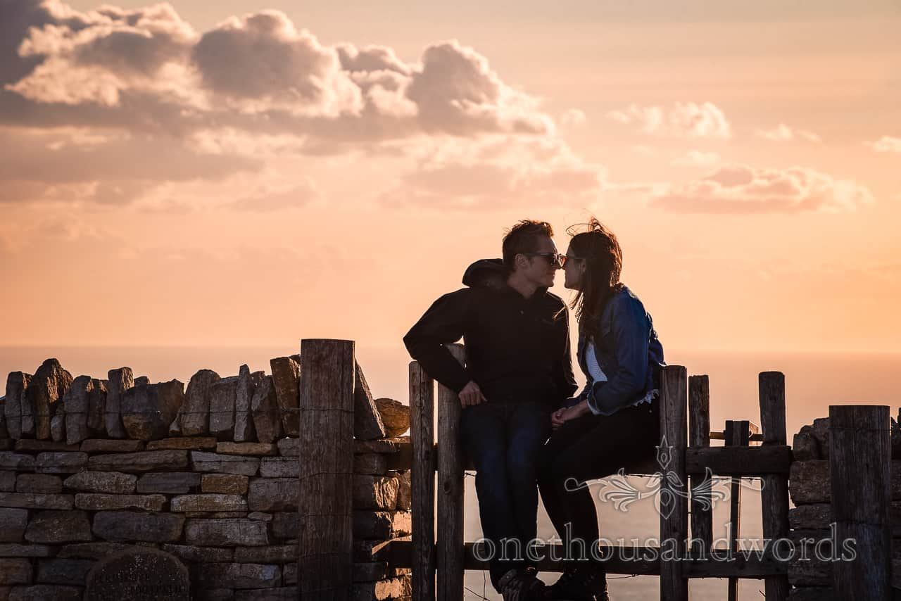 Couple kissing on wooden stile in Dorset countryside