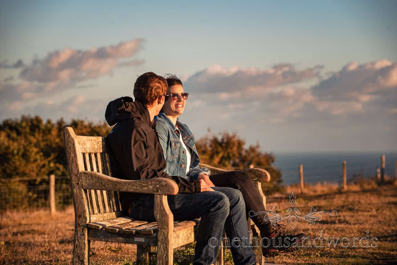 happy couple in sunglasses sit on bench in Dorset countryside by the sea
